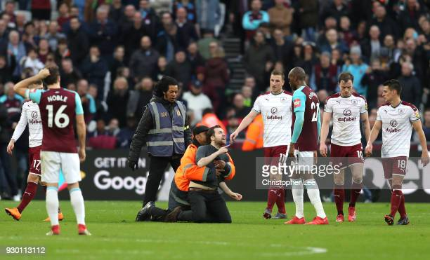 A pitch invader confronts Angelo Ogbonna of West Ham United whilst he is tackled by a steward during the Premier League match between West Ham United...