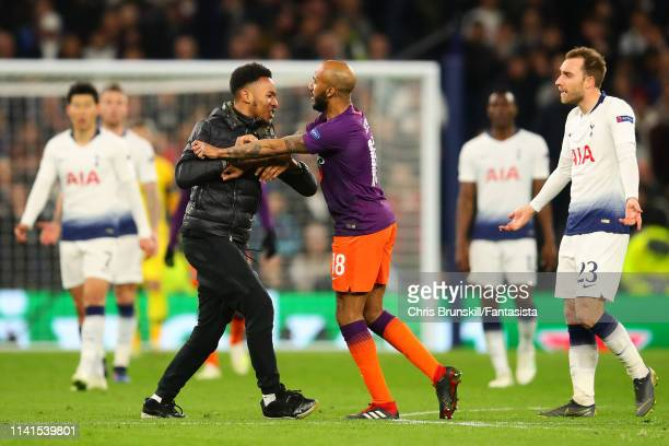 Pitch invader confronts Fabian Delph of Manchester City during the UEFA Champions League Quarter Final first leg match between Tottenham Hotspur and...