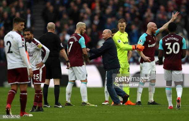 A pitch invader confronts Marko Arnautovic of West Ham United on the pitch during the Premier League match between West Ham United and Burnley at...