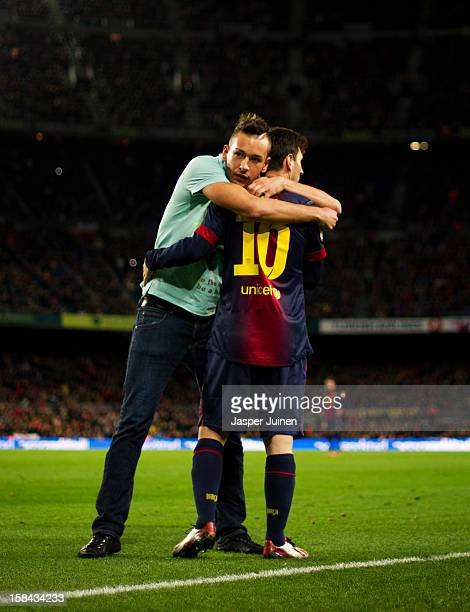 Pitch invader embraces Lionel Messi of Barcelona during the la Liga match between FC Barcelona and Club Atletico de Madrid at the Camp Nou stadium on...