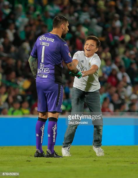 A pitch invader greets Jonathan Orozco of Santos during the 17th round match between Santos Laguna and America as part of the Torneo Apertura 2017...