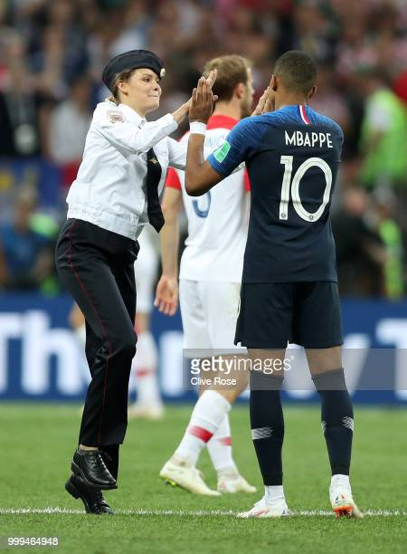 A pitch invader high fives Kylian Mbappe of France during the 2018 FIFA World Cup Final between France and Croatia at Luzhniki Stadium on July 15...