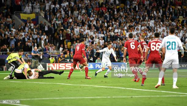 Pitch invader is apprehended as Cristiano Ronaldo of Real Madrid runs with the ball during the UEFA Champions League Final between Real Madrid and...