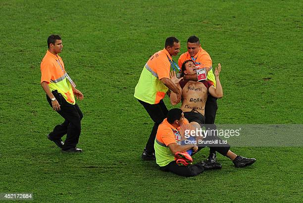 A pitch invader is apprehended by security stewards during the 2014 World Cup Final match between Germany and Argentina at Maracana Stadium on July...