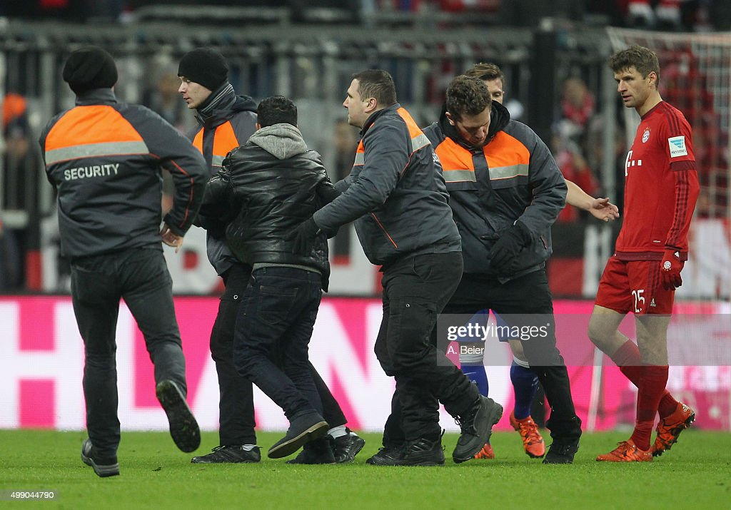 A pitch invader is arrested after he hugged Thomas Mueller (R) of Bayern Muenchen during the Bundesliga match between FC Bayern Muenchen and Hertha BSC at Allianz Arena on November 28, 2015 in Munich, Germany.