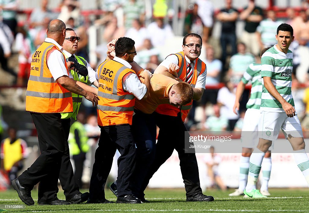 A pitch invader is carried off during a pre season friendly match between Brentford and Celtic at Griffin Park on July 20, 2013 in Brentford, England.
