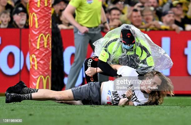 Pitch invader is caught by security guards during the 2020 AFL Grand Final match between the Richmond Tigers and the Geelong Cats at The Gabba on...