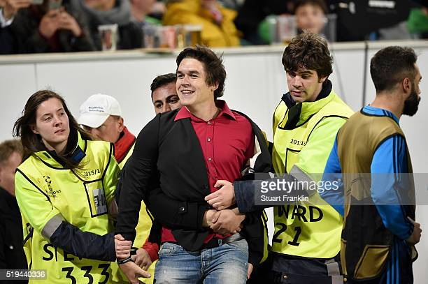 A pitch invader is caught by stewards during the UEFA Champions League Quarter Final First Leg match between VfL Wolfsburg and Real Madrid at...