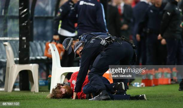 A pitch invader is dealt with by police during the International Friendly match between Sydney FC and Liverpool FC at ANZ Stadium on May 24 2017 in...
