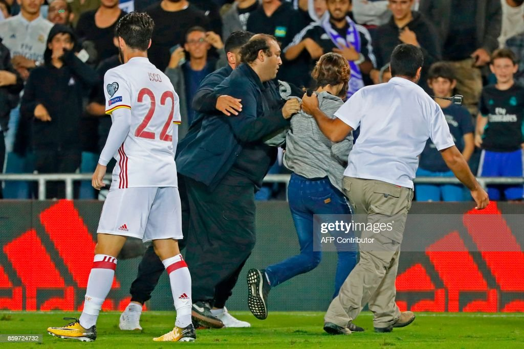 A pitch invader is detained by securiy during the Russia 2018 FIFA World Cup European Group G qualifying football match between Israel and Spain at Teddy Stadium in Jerusalem on October 9, 2017. Israeli police denied local media reports that the pitch invader who ran towards Spanish attacker Isco during a World Cup qualifier was carrying a knife. The Israeli news website Ynet cited security officials in the stadium as saying six fans entered the field at the end of the game, with one of them carrying a small knife in his sock. GUEZ