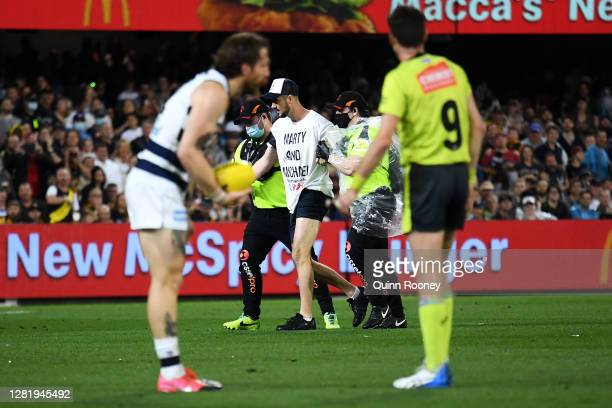 Pitch invader is escorted from the field by security during the 2020 AFL Grand Final match between the Richmond Tigers and the Geelong Cats at The...