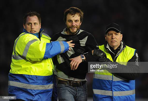 A pitch invader is escorted from the ground during the FA Cup third round match between Brighton Hove Albion and Wrexham at Amex Stadium on January 7...