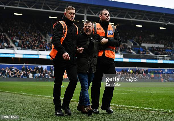 A pitch invader is escorted from the ground during the Sky Bet Championship match between Queens Park Rangers and Aston Villa at Loftus Road on...