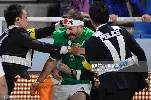 TOPSHOT A pitch invader is escorted off the field after the Japan 2019 Rugby World Cup Pool A match between Ireland and Samoa at the Fukuoka...