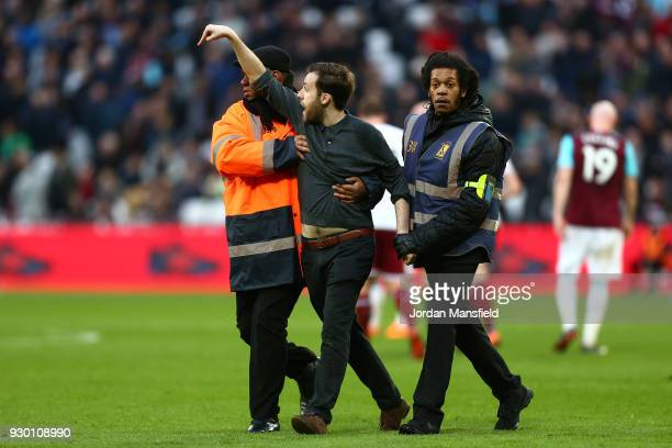 A pitch invader is escorted off the pitch during the Premier League match between West Ham United and Burnley at London Stadium on March 10 2018 in...