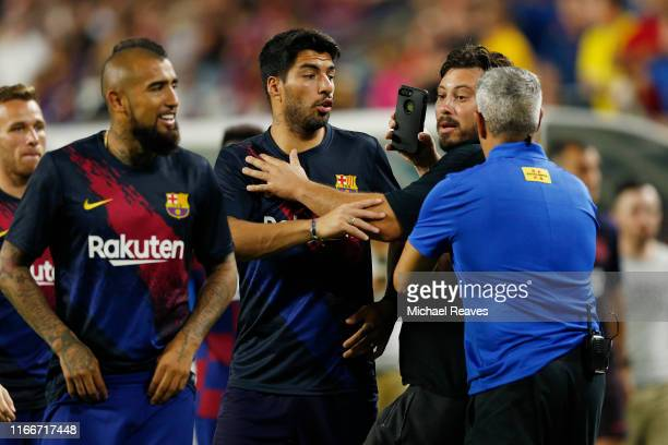 A pitch invader is grabbed by security while trying to approach Luis Suarez of Barcelona after the game between FC Barcelona and SSC Napoli preseason...