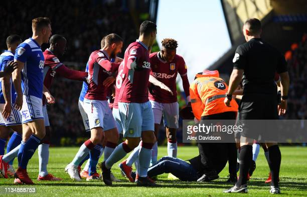 A pitch invader is hauled out a players huddle during the Sky Bet Championship match between Birmingham City and Aston Villa at St Andrew's Trillion...