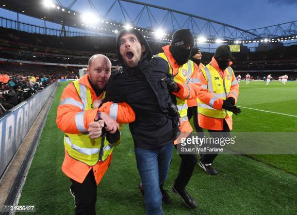 A pitch invader is lead away by stewards during the Premier League match between Arsenal FC and Manchester United at Emirates Stadium on March 10...