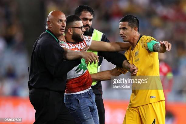 A pitch invader is pulled away from Tim Cahill of Australia during the International Friendly Match between the Australian Socceroos and Lebanon at...