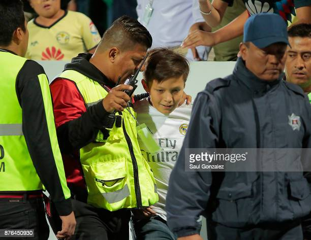 A pitch invader is removed by security during the 17th round match between Santos Laguna and America as part of the Torneo Apertura 2017 Liga at...