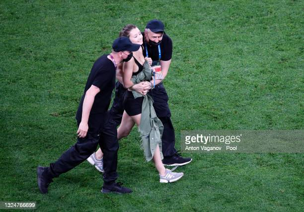 Pitch invader is removed from the pitch by ground staff during the UEFA Euro 2020 Championship Group B match between Finland and Belgium at Saint...