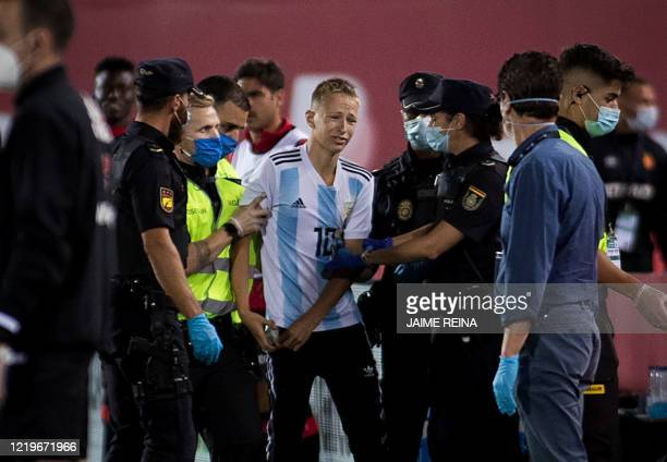 A pitch invader is removed from the pitch during the Spanish League football match between RCD Mallorca and FC Barcelona at the Visit Mallorca...