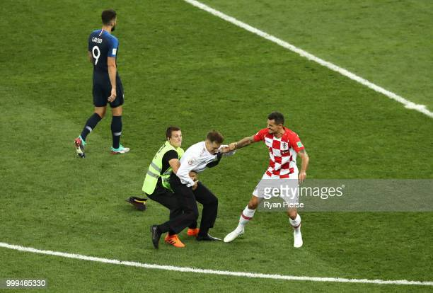 A pitch invader is stopped by Dejan Lovren of Croatia during the 2018 FIFA World Cup Final between France and Croatia at Luzhniki Stadium on July 15...