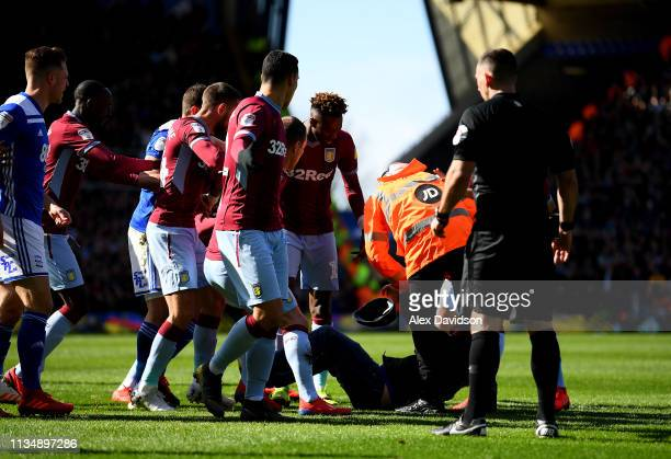 A pitch invader is tackled by a steward after striking Jack Grealish of Aston Villa during the Sky Bet Championship match between Birmingham City and...