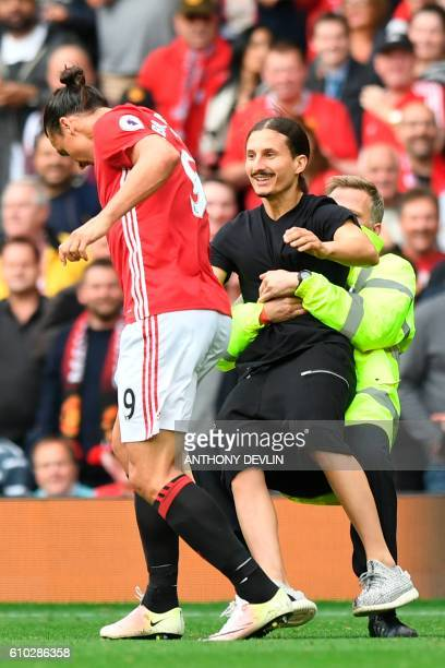 A pitch invader is tackled by a steward as he tries to reach Manchester United's Swedish striker Zlatan Ibrahimovic during the English Premier League...