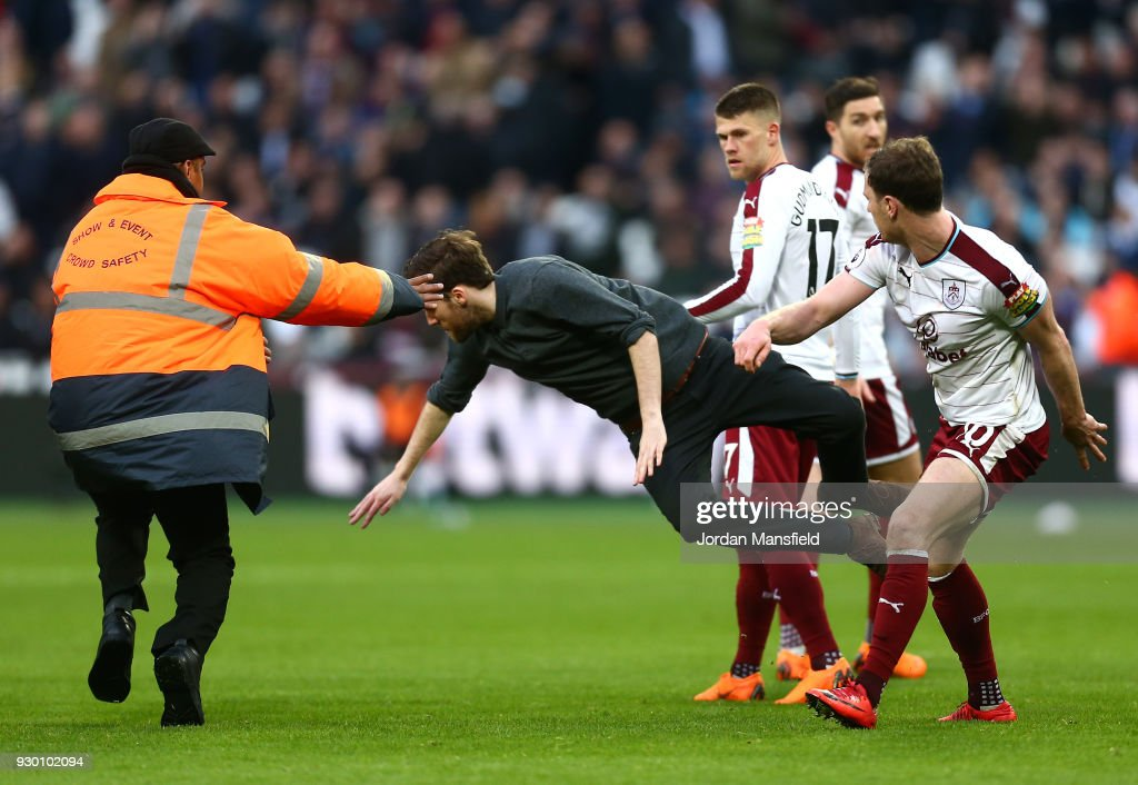 A pitch Invader is tackled by a steward, Johann Gudmundsson of Burnley and Ashley Barnes of Burnley during the Premier League match between West Ham United and Burnley at London Stadium on March 10, 2018 in London, England.