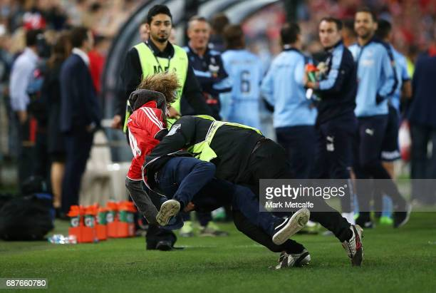 A pitch invader is tackled by security during the International Friendly match between Sydney FC and Liverpool FC at ANZ Stadium on May 24 2017 in...