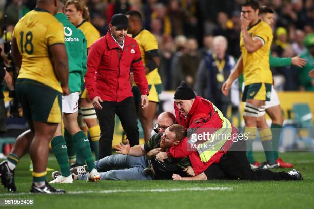 A pitch invader is tackled by security staff during the Third International Test match between the Australian Wallabies and Ireland at Allianz...