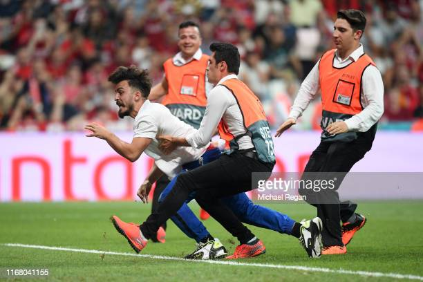 A pitch invader is taken down by security during the UEFA Super Cup match between Liverpool and Chelsea at Vodafone Park on August 14 2019 in...