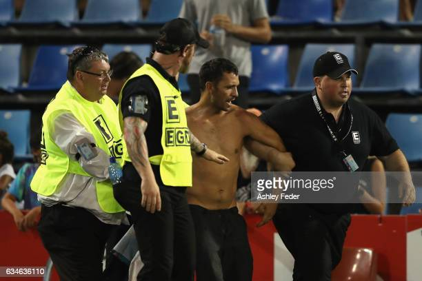 A pitch invader is walked off by security during the NRL All Stars match between the 2017 Harvey Norman All Stars and the NRL World All Stars at...
