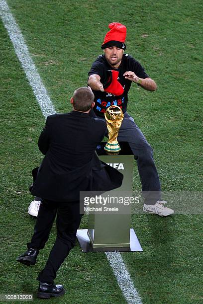 Pitch invader, Jimmy Jump, is wrestled away from the World Cup by security ahead of the 2010 FIFA World Cup South Africa Final match between...