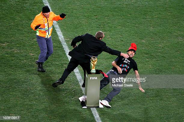 A pitch invader Jimmy Jump is wrestled away from the World Cup by security ahead of the 2010 FIFA World Cup South Africa Final match between...