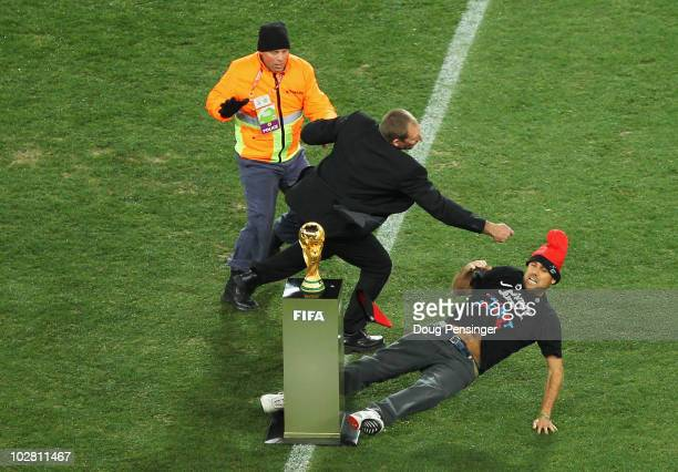 Pitch invader, Jimmy Jump, is wrestled away from the World Cup Trophy by security, prior to the 2010 FIFA World Cup South Africa Final match between...