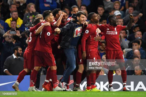 A pitch invader joins in as Daniel Sturridge of Liverpool celebrates with teammates after scoring the equalising goal during the Premier League match...