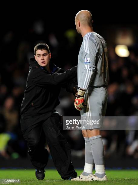 A pitch invader pats Pepe Reina of Liverpool during the Barclays Premier League match between Chelsea and Liverpool at Stamford Bridge on February 6...
