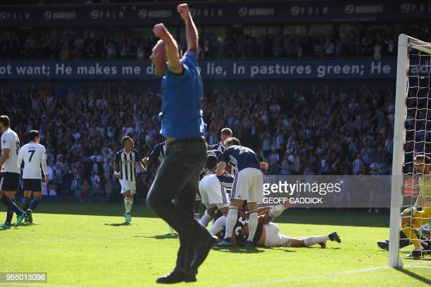 A pitch invader reacts as West Bromwich Albion's English midfielder Jake Livermore is mobbed by teammates as he celebrates scoring the opening goal...