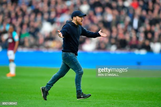 A pitch invader runs onto the pitch during the English Premier League football match between West Ham United and Burnley at The London Stadium in...