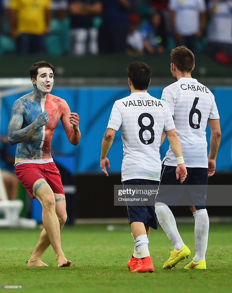 A pitch invader runs woard Mathieu Valbuena and Yohan Cabaye of France during the 2014 FIFA World Cup Brazil Group E match between Switzerland and France at Arena Fonte Nova on June 20, 2014 in Salvador, Brazil.