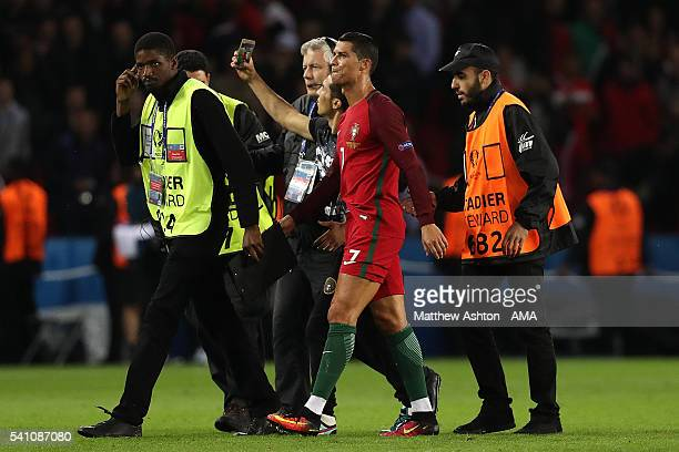 A pitch invader takes a selfie with Cristiano Ronaldo of Portugal at the end of the UEFA EURO 2016 Group F match between Portugal and Austria at Parc...