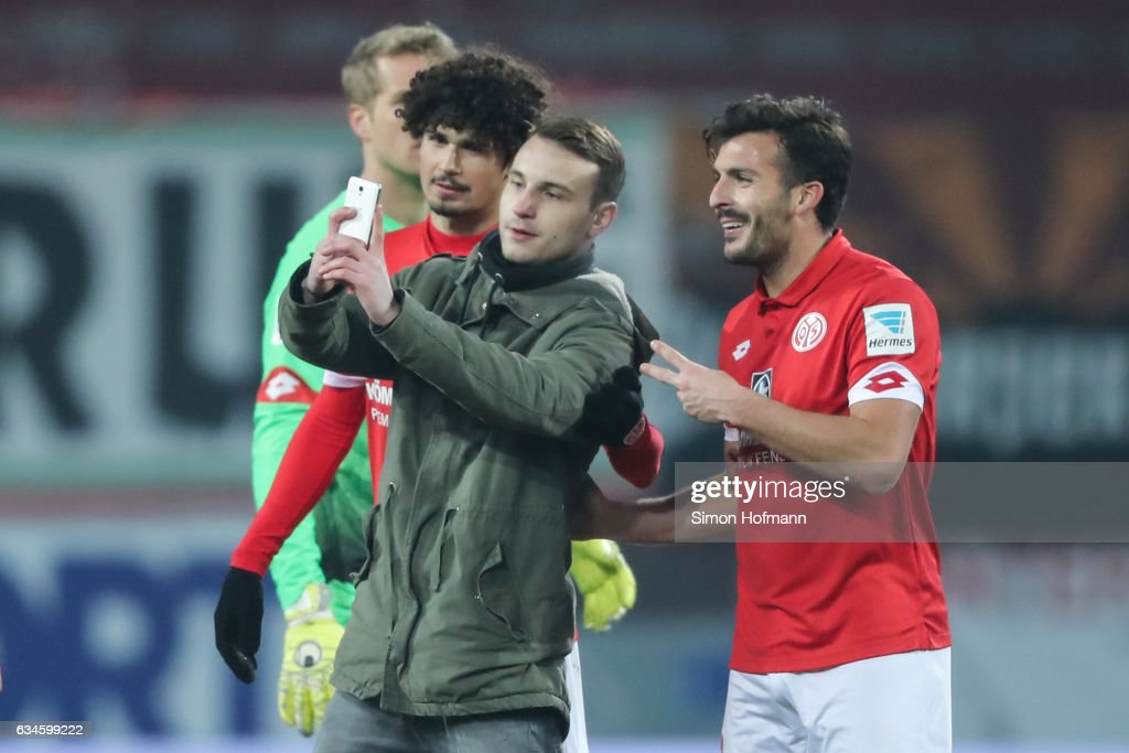 A pitch invader takes a selfie with Giulio Donati of Mainz (R) during the Bundesliga match between 1. FSV Mainz 05 and FC Augsburg at Opel Arena on February 10, 2017 in Mainz, Germany.