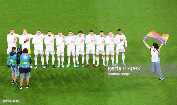 Pitch invader with a rainbow flag is seen on the pitch as the players of Hungary sing the national anthem prior to the UEFA Euro 2020 Championship...