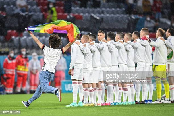 Pitch invader with a rainbow flag is seen on the pitch as the players line up prior to the UEFA Euro 2020 Championship Group F match between Germany...
