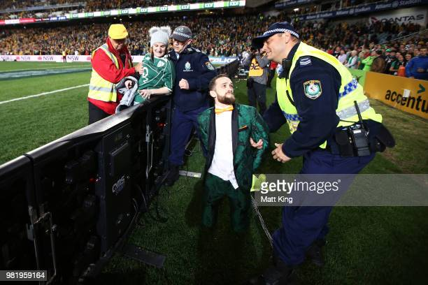 Pitch invaders are detained by security staff and police during the Third International Test match between the Australian Wallabies and Ireland at...