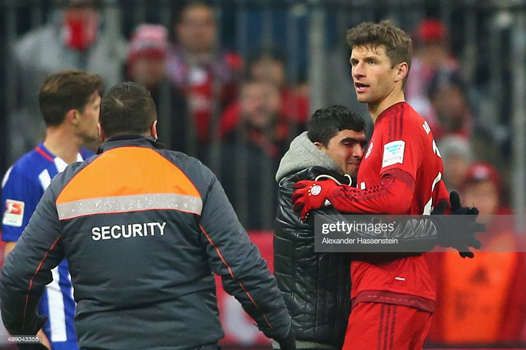 A pitch invaders hugs Thomas Mueller of Muenchen during the Bundesliga match between FC Bayern Muenchen and Herha BSC Berlin at Allianz Arena on November 28, 2015 in Munich, Germany.