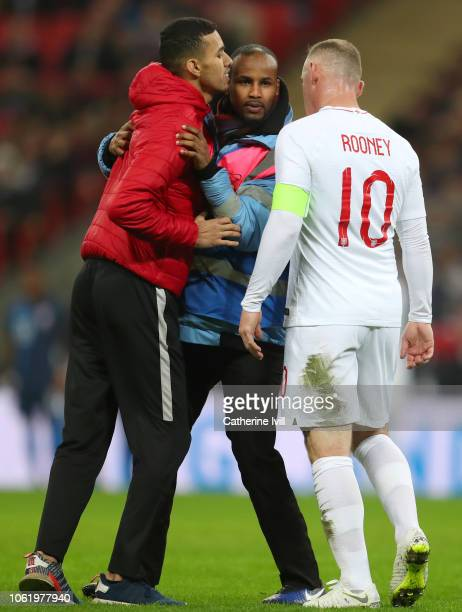A pitch invador attempts to embrace Wayne Rooney of England as a steward tackles him during the International Friendly match between England and...