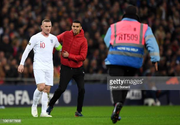 A pitch invador attempts to embrace Wayne Rooney of England during the International Friendly match between England and United States at Wembley...